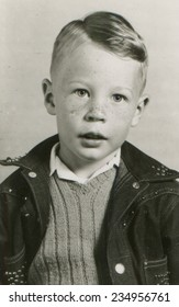 CANADA - CIRCA 1950s: An antique photo shows portrait of a freckled boy in denim jacket