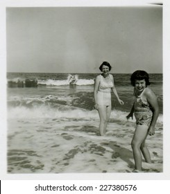 CANADA - CIRCA 1950s: Vintage photo shows mother and her daughter swimming in the sea.