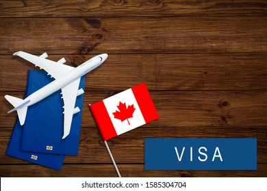 Canada concept. Text near passport cover and canadian flag, hammer on dark wooden background top view