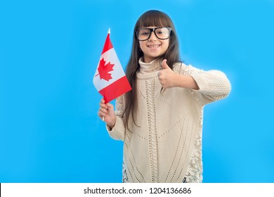 Canada is cool! Portrait happy little girl with Canadian flag showing thumbs up standing over blue background.