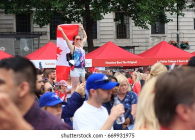 Canada Day celebrations 2017 in Trafalgar Square in London.  Crowds of happy people wearing Canadian colours and sporting Canadian flags enjoy canadian music, comedy, and beer in the sunshine.