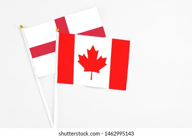 Canada and England stick flags on white background. High quality fabric, miniature national flag. Peaceful global concept.White floor for copy space.