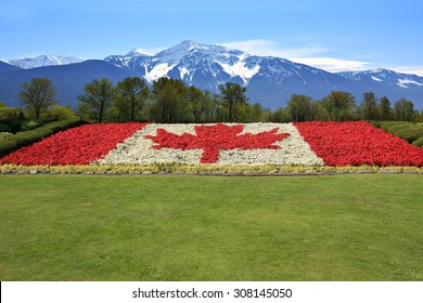 Canada flag done in red and white begonia flower against a backdrop of the Rocky mountains.