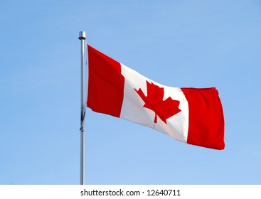 canada flag flying on blue sky