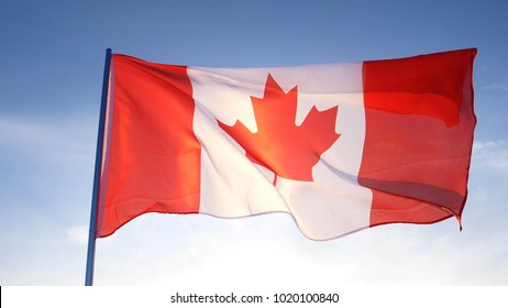 Canada flag on clear blue sky with sun