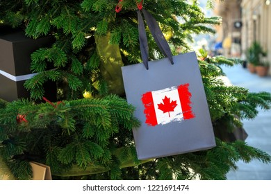 Canada flag printed on a Christmas shopping bag. Close up of a shopping bag as a decoration on a Xmas tree on a street in Canada. Christmas shopping, local market sale and deals concept.