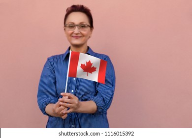 Canada flag. Woman holding Canadian flag. Selective focus. Nice portrait of middle aged lady 40 50 years old with a national flag over pink wall background. Visit Canada / immigrate to Canada concept.