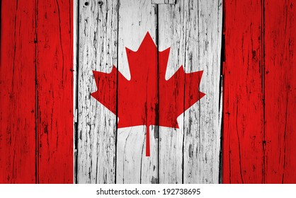 Canada grunge wood background with Canadian flag painted on aged wooden wall.