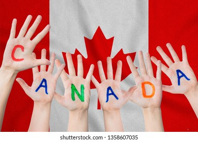 Canada inscription on the children's hands against the background of a waving flag of the Canada.