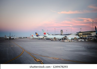 Canada, Montreal - 17. 09. 2018. Panoramic view of modern international airport with airplanes in row under sunset sky