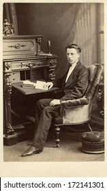 CANADA - MONTREAL - CIRCA 1868 A vintage Cartes de visite photo of a young gentleman. The man is sitting in front of a desk with a book. A photo from the Victorian era. CIRCA 1868
