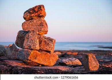 Canada, Nunavut, Territory, Setting sun lights stone cairns on Harbour Islands along Hudson Bay near Arctic Circle