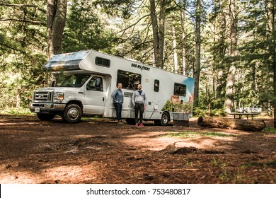 Canada Ontario Algonquin National Park 30.09.2017 - couple in front of Parked RV camper car at Lake of two rivers Campground Beautiful natural forest Cruise America