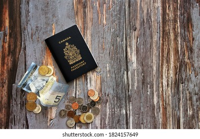 A Canada passport with Canadian currency laid out on a rustic wooden piece