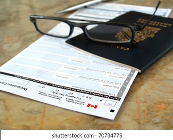 Canada passport on declaration card with glasses and pen