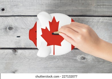 Canada saving concept with little hand dropping a coin into piggy bank overlaid with Canadian flag