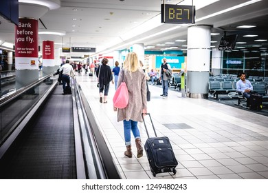 Canada, Toronto - 17. 09. 2018. Back view of woman walking with suitcase in modern hall of airport for boarding