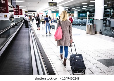 Canada, Toronto - 17. 09. 2018. Back view of casual woman with black suitcase walking in corridor of airport