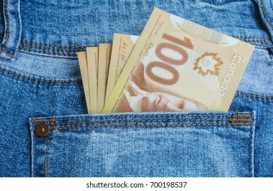 Canadian banknotes are in the back pocket of blue jeans.