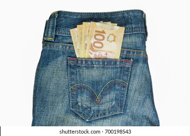 Canadian banknotes are in the back pocket of blue jeans isolated on white background.