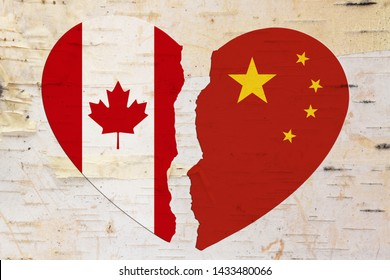 Canadian and Chinese flags in a broken heart over weathered wood