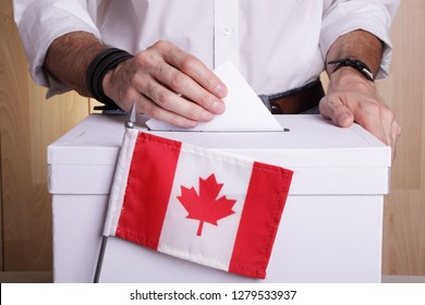 A Canadian citizen inserting a ballot into a ballot box. Canada flag in front of it