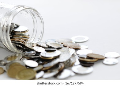 Canadian Coins Spilling Out Of Glass Container