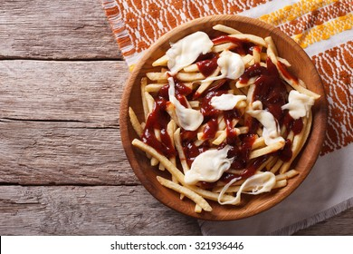 Canadian cuisine: poutine with sauce and cheese on the table. horizontal view from above