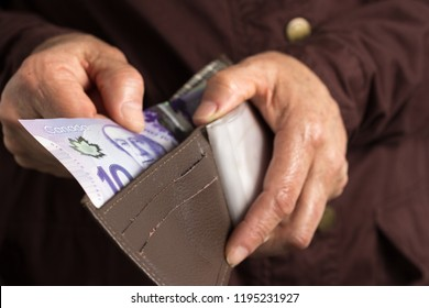 Canadian currency. Dollars. Money from Canada. Old retired person paying in cash.