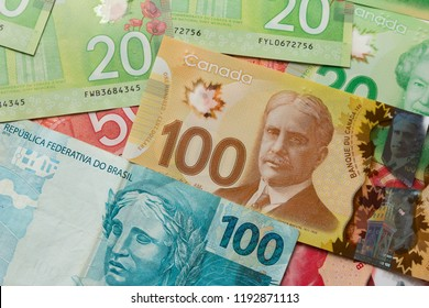 Canadian Dollars and Brazilian currency. Money from Canada and Brazil. Full frame of bills spread on table and assorted amounts.