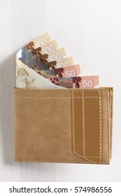 Canadian Dollars and credit cards in mustard coloured leather wallet