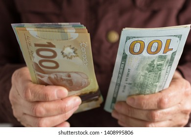 Canadian Dollars and North American currency. Money from Canada and United States. Front view senior person holding bills.