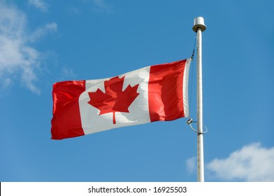 Canadian flag against a blue sky.