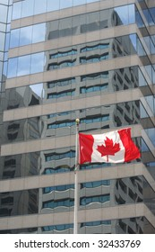Canadian flag billowing in the wind outside a glass fronted skyscraper