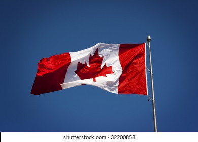Canadian Flag Blowing in the wind against a rich blue background