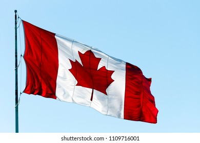Canadian flag blowing in the wind with blue sky and copy space.