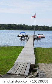 A Canadian flag flutters over a long wooden dock where boats are moored on quiet water.