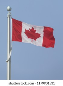 Canadian flag flying against clear blue sky