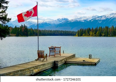 Canadian flag flying on the dock in foreground of Lake Edith Alberta, with a chair and bench, pine trees line the shore and mountains of the Canadian rockies in the background with blue sky and clouds