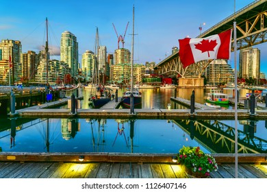 Canadian flag in front of view Ferry boat docked in Granville island at twilight in Vancouver,Canada