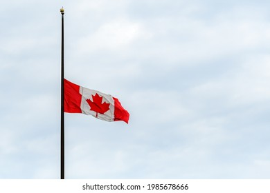 A Canadian flag at half mast, lowered in remembrance of the indigenous children who were abused and died in residential schools. Overcast, wide view.