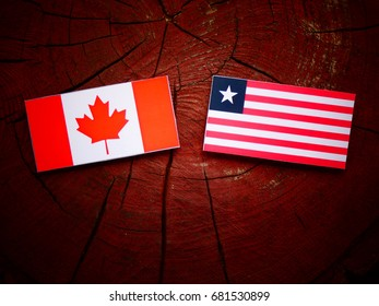 Canadian flag with Liberian flag on a tree stump isolated