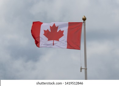 The Canadian flag on a flag pole blowing in the wind