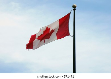 A Canadian Flag slightly torn due to the high constant winds at it's location