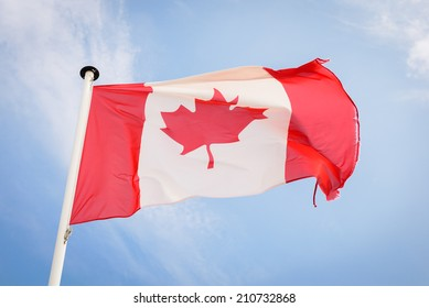 Canadian flag waving against blue sky