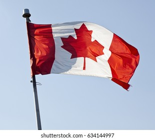 Canadian flag waving against blue sky.