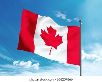 Canadian flag waving in the blue sunny sky