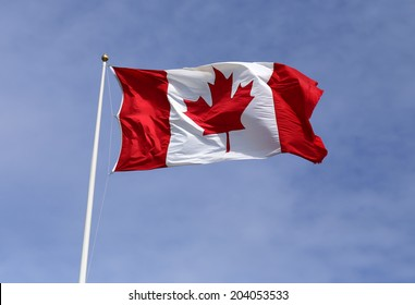 The Canadian flag waving in the breeze under a blue sky.