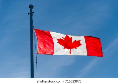 Canadian flag waving over blue sky in Victoria, Canada