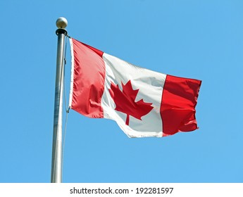 A Canadian flag waving in the wind against a blue sky